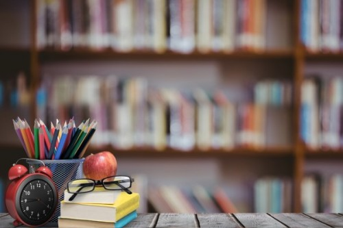 School materials and apple with library background