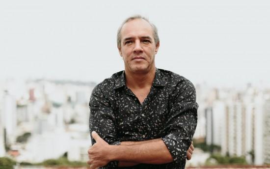Retrato de Flávio Henrique Alves, de camisa estampada e braços cruzados, olhando para a câmera.