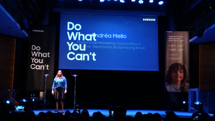 """Imagem de Andréa Mello no palco. Na tela, está escrito o lema da campanha, em letras grandes, """"Do What You Can't"""""""