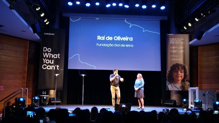 """Imagem do palco, onde estão o ex-jogador Raí e Andréa Mello. Na tela azul em cima do palco está escrito """"Raí de Oliveira, Fundação Gol de Letra"""""""