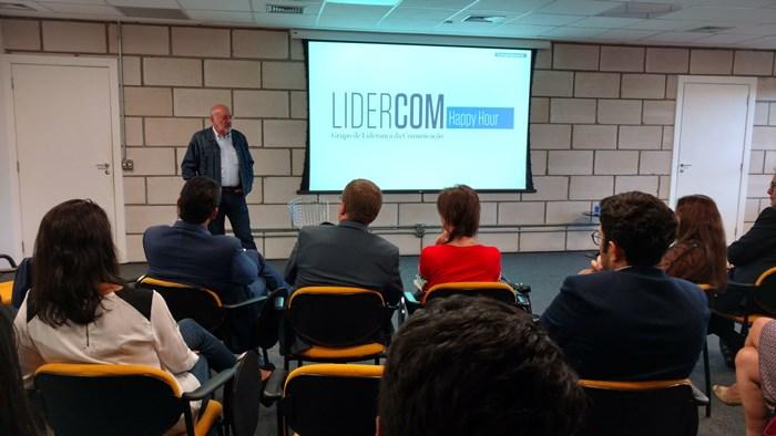 """Foto de Pedro Herz em pé, de frente para a plateia. Na tela, está projetado a marca do Lidercom, ao lado da marca, encontra-se uma caixa azul escrito """"Happy hour""""."""