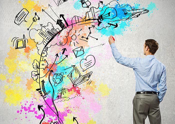 Profissional vestido com camisa e calça social está voltado à frente de uma parede. Ele desenha formas e cores