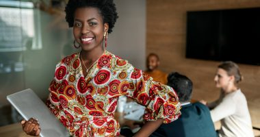 Beautiful young smiling professional black african business woman holding laptop, coworkers hold a meeting in background